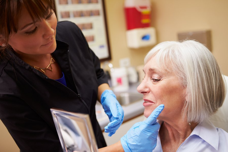 Nurse practitioners giving female patient a facial consult