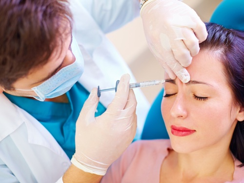 male physician injecting botox into female patient